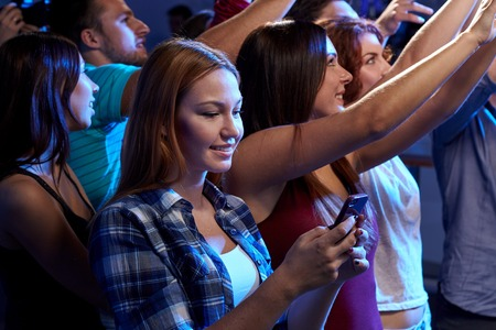 live concert: party, holidays, celebration, nightlife and people concept - smiling young woman with smartphone texting message at concert in club