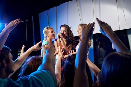 gente cantando: fiesta, días de fiesta, celebración, vida nocturna y la gente concepto - mujeres jóvenes felices cantando karaoke en club nocturno Foto de archivo