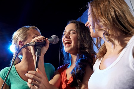 cantando: fiesta, días de fiesta, celebración, vida nocturna y la gente concepto - mujeres jóvenes felices cantando karaoke en club nocturno Foto de archivo