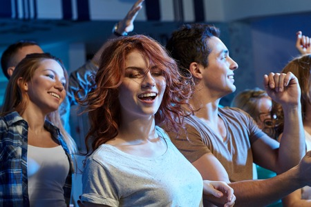 rap: party, holidays, nightlife and people concept - happy friends dancing at night club Stock Photo