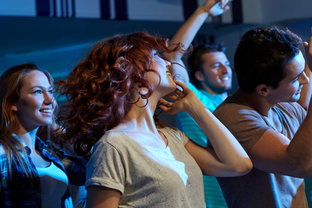 rap music: party, holidays, nightlife and people concept - happy friends dancing at night club Stock Photo