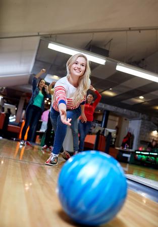 사람들, 레저, 스포츠 및 엔터테인먼트 개념 - 볼링 클럽에서 행복 젊은 여자가 던지는 공