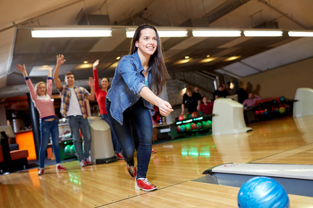 leisure activities: people, leisure, sport and entertainment concept - happy young woman throwing ball in bowling club