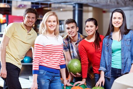 people, leisure, sport, friendship and entertainment concept - happy friends in bowling club photo