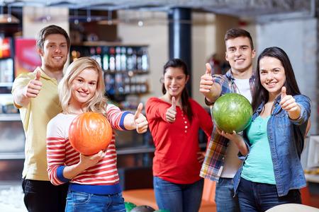 bolos: la gente, el ocio, el deporte, la amistad y el concepto de entretenimiento - amigos felices que sostienen bolas y mostrando los pulgares para arriba en el club de bolos Foto de archivo