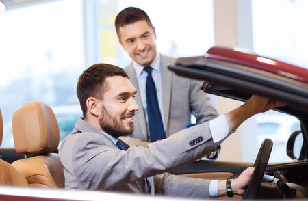 car rental: auto business, car sale, consumerism and people concept - happy man with car dealer in auto show or salon Stock Photo