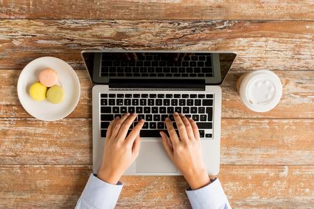 bedrijfsleven, onderwijs, mensen en technologie concept - close-up van vrouwelijke handen met laptop computer, koekjes en kopje koffie op tafel Stockfoto