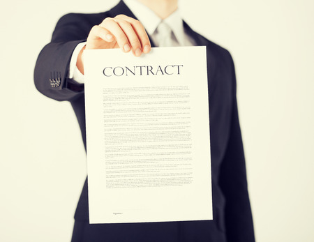 new contract: picture of man hands holding contract with random text