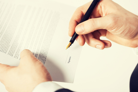 legal services: picture of man hands signing contract with random text Stock Photo