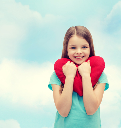 big girl: love, happiness and people concept - smiling little girl with red heart