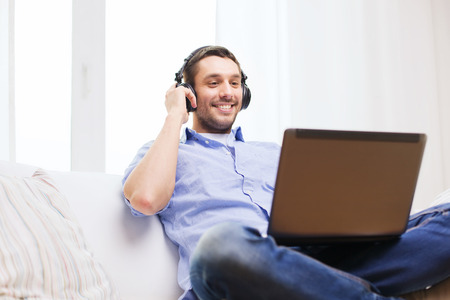 technology, home, music and lifestyle concept - smiling man with laptop and headphones at home Stock Photo