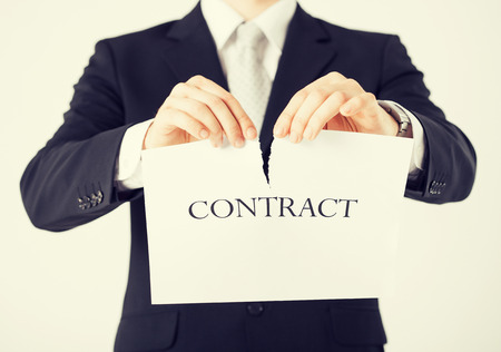 broken contract: picture of man hands tearing contract paper