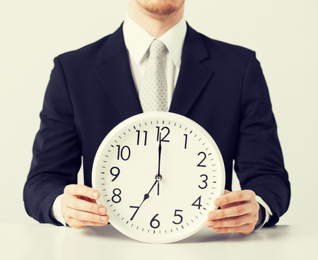 rushing hour: close up of man holding wall clock