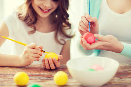 kids activities: easter, family, holiday and child concept - close up of little girl and mother coloring eggs for easter