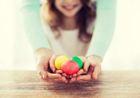 huevo: Pascua, la familia, las vacaciones y los ni�os concepto - huevos cerca de la ni�a y de la madre explotaci�n de colores