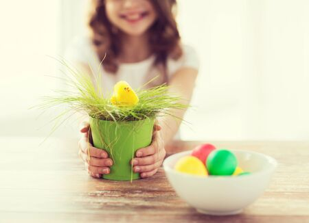 young girl: easter, holiday and child concept - close up of girl holding pot with green grass and yellow chiken toy with bowl of colored eggs