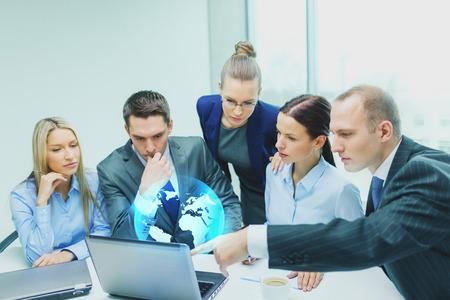 dirección empresarial: los negocios, la tecnología mundial y la gente concepto - equipo de negocios serio con los ordenadores portátiles y virtuales globo de proyección que tiene la discusión en la oficina Foto de archivo