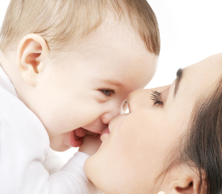 family and happy people concept - mother kissing her baby Stock Photo
