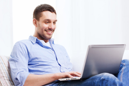 technology, home, people and lifestyle concept - smiling man working with laptop at home Stock Photo