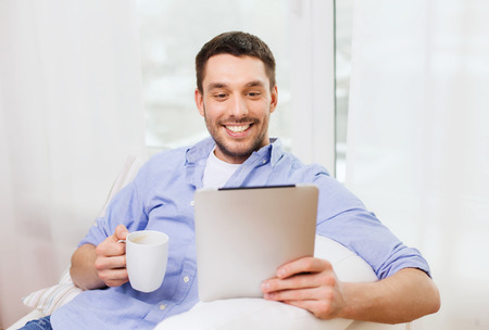 기술, 사람과 레저 개념 - 잘 생긴 남자 태블릿 pc 컴퓨터와 컵 마시는 커피 또는 차 집에서