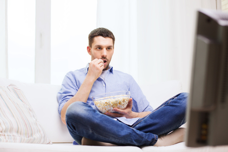 popcorn bowls: sports, food, happiness and people concept - man watching tv and eating popcorn at home