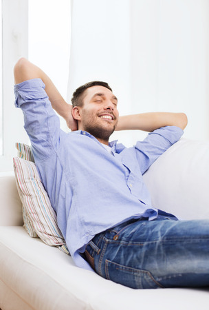 rest and relaxation: people and leisure concept - smiling man with closed eyes relaxing on couch at home