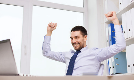 cheering people: business, people, technology and work concept - smiling businessman sitting in front of laptop with raised hands and cheering in office