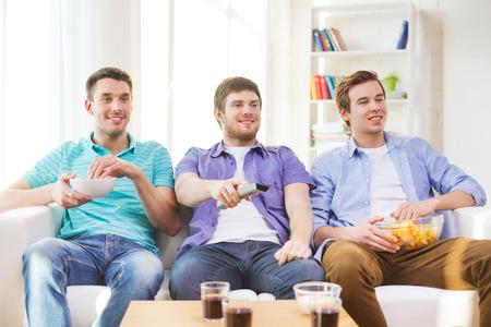 cerillos: amistad, deportes y concepto de entretenimiento - amigos hombres felices con aperitivos viendo televisi�n en casa Foto de archivo