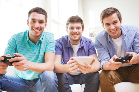 gamers: friendship, technology, games and home concept - smiling male friends playing video games at home