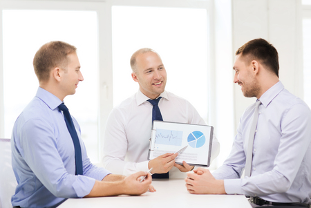 audit: business and office concept - smiling businessman showing others charts in office