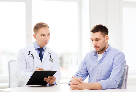 urologist: healthcare and medicine concept - serious doctor with clipboard and patient in hospital