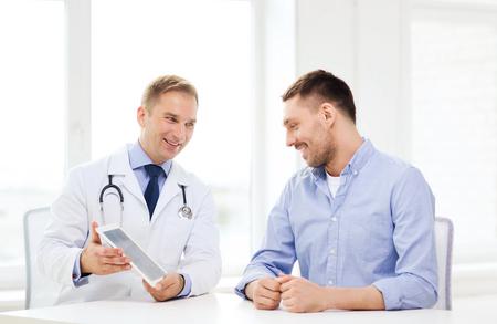 gezondheidszorg, technologie en geneeskunde concept - lachende arts met een tablet-pc computer en patiënt in het ziekenhuis