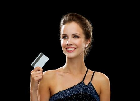caras emociones: riqueza, dinero, el lujo y el concepto de la gente - la mujer sonriente en traje de noche con tarjeta de crédito sobre fondo negro