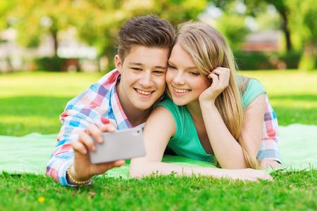 haciendo el amor: vacaciones, días de fiesta, la tecnología y la amistad concepto - sonriente pareja en Manta y haciendo Autofoto con el teléfono inteligente en el parque