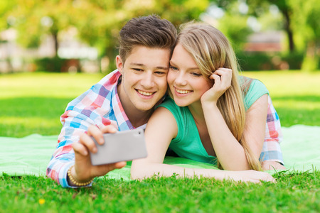 vacation, holidays, technology and friendship concept - smiling couple lying on blanket and making selfie with smartphone in park photo