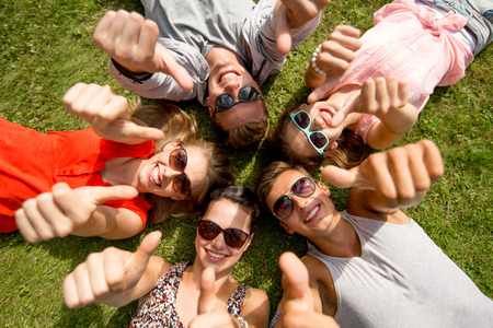 approvement: friendship, leisure, summer, gesture and people concept - group of smiling friends lying on grass in circle and showing thumbs up outdoors Stock Photo