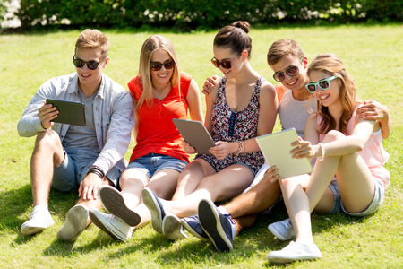 group picture: friendship, leisure, summer, technology and people concept - group of smiling friends with tablet pc computers sitting on grass in park