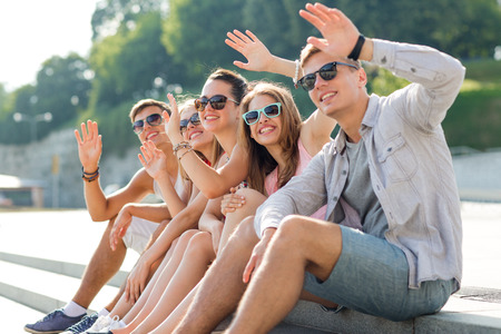 friendship, leisure, summer, gesture and people concept - group of smiling friends sitting on city square photo