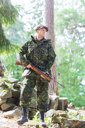 infantryman: young soldier, ranger or hunter with gun in forest Stock Photo