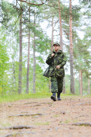corps: young soldier, ranger or hunter with gun walking in forest