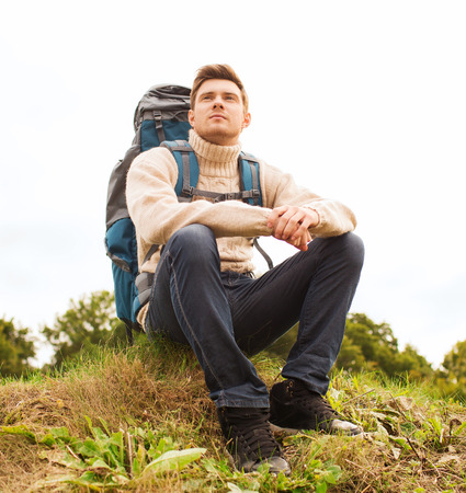 sitting on the ground: man with backpack sitting on ground Stock Photo