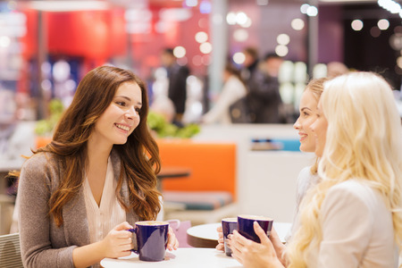 happy young women with coffee cups sitting at table and talking in mall or cafe photo