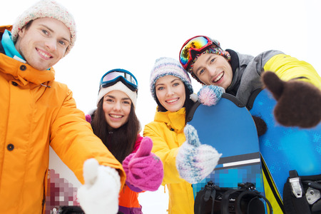 happy friends with snowboards showing thumbs up photo