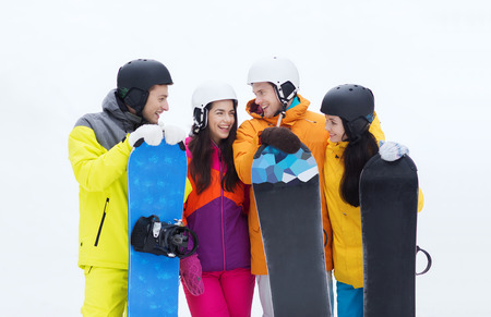 happy friends in helmets with snowboards talking photo