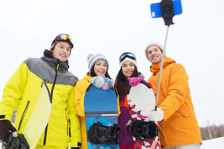 happy friends with snowboards and smartphone taking selfie photo