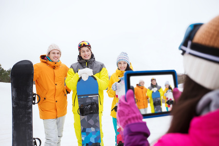 happy friends with snowboards and tablet pc computer taking picture outdoors photo