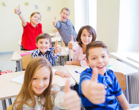 learners: group of school kids sitting in classroom and showing thumbs up