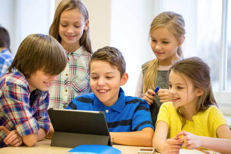 niños jugando en la escuela: grupo de niños de la escuela con la computadora Tablet PC que se divierte en descanso en el aula