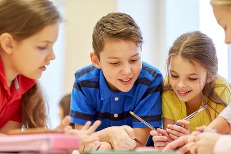 primární: Skupina školní děti s pera a papíry psaní v učebně
