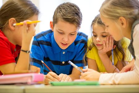 groep van school kinderen met pennen en papier schrijven in klas